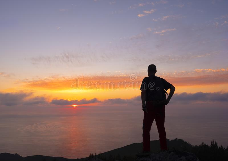Homber doing sports on the top, facing the blue sky and the sunset on the sea royalty free stock photos