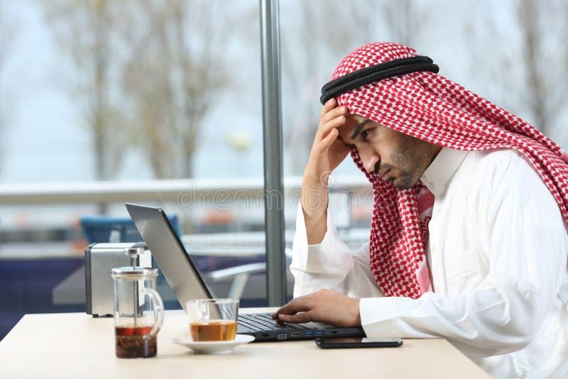 Hombre árabe confuso que comprueba el ordenador portátil en una barra foto de archivo