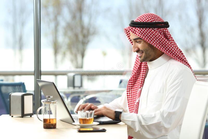 Hombre árabe del saudí que trabaja en línea con un ordenador portátil fotografía de archivo libre de regalías