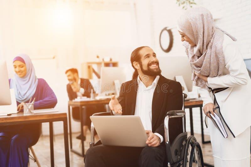 Hombre árabe discapacitado en la silla de ruedas que trabaja en oficina El hombre está hablando con el compañero de trabajo femen fotos de archivo libres de regalías