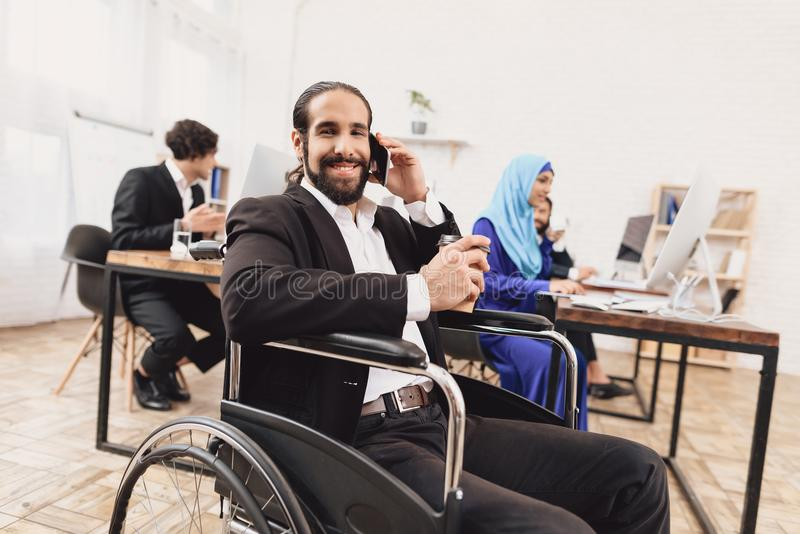 Hombre árabe discapacitado en la silla de ruedas que trabaja en oficina El hombre está hablando en el teléfono y el café de consu imagen de archivo