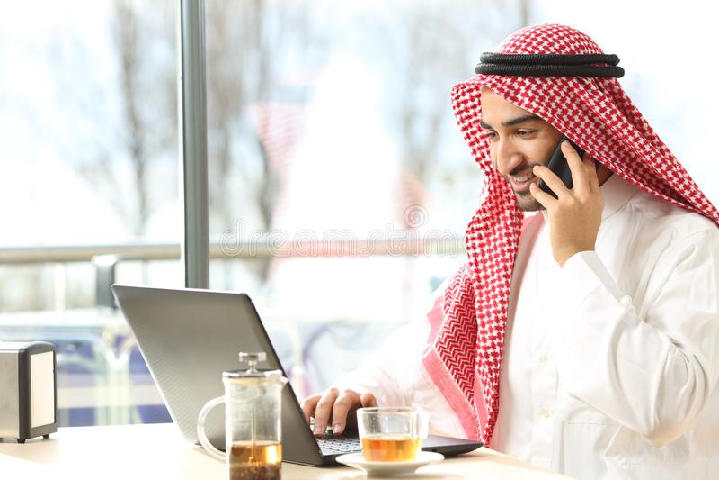Hombre árabe feliz usando un ordenador portátil y el hablar en el teléfono en una barra imagenes de archivo