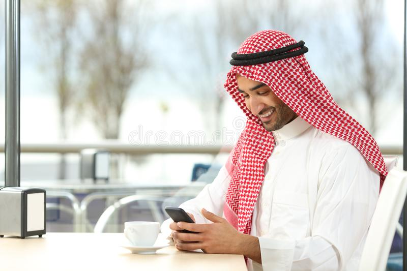 Hombre árabe feliz usando un teléfono elegante en una cafetería fotografía de archivo