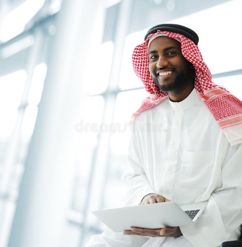 Hombre árabe negro que trabaja en la computadora portátil foto de archivo libre de regalías