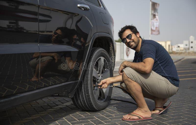 Hombre árabe que infla el neumático del coche fotografía de archivo