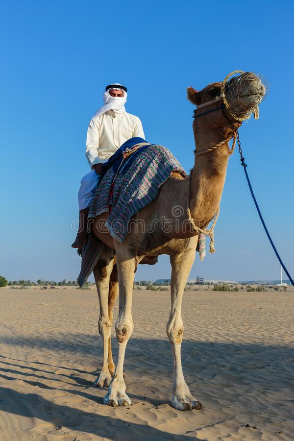 Hombre árabe que monta un camello en desierto imágenes de archivo libres de regalías