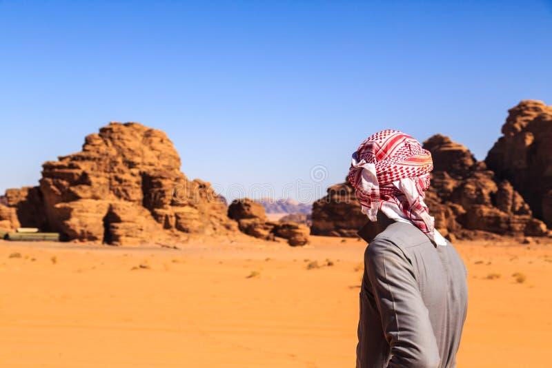 Hombre árabe visto de detrás en el desierto de Wadi Rum imagen de archivo libre de regalías