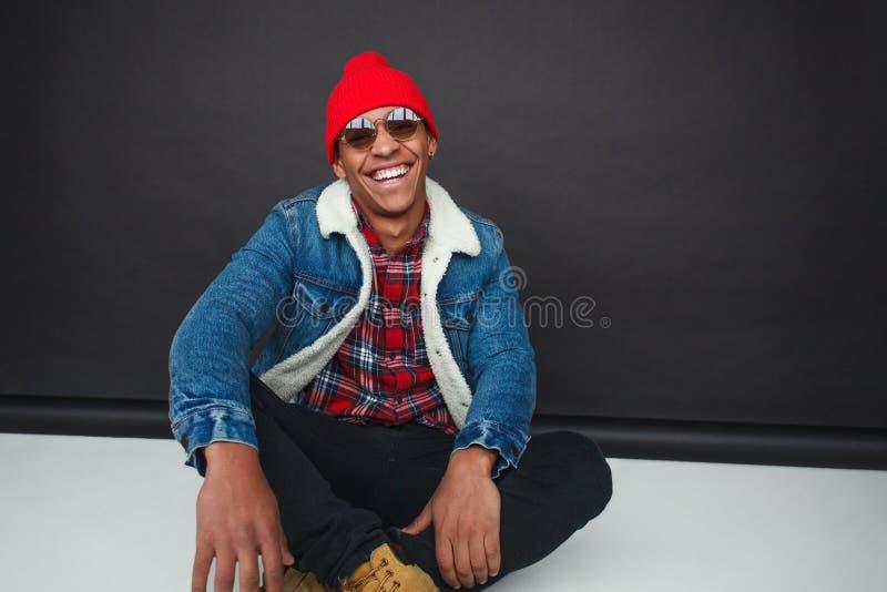 Hombre étnico de moda de risa en estudio imagen de archivo