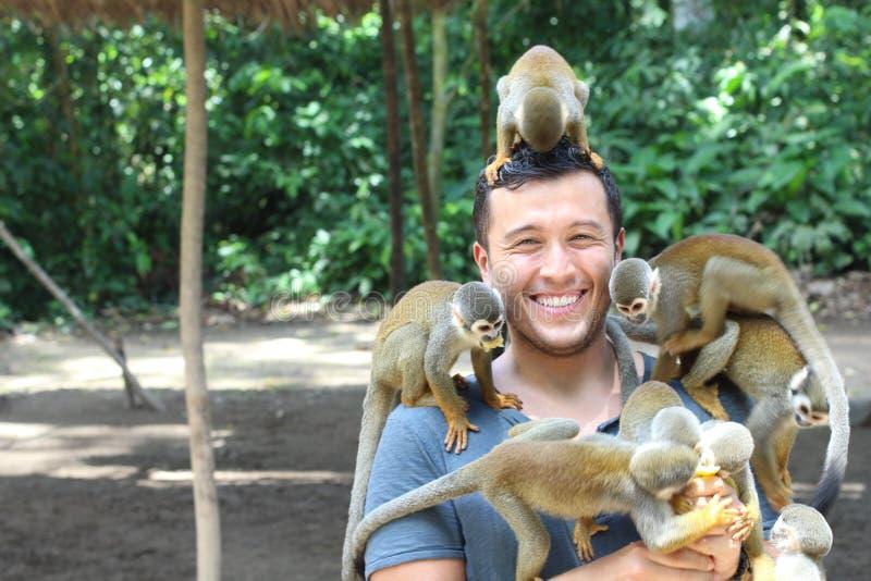 Hombre étnico hermoso con los monos de titi imagen de archivo