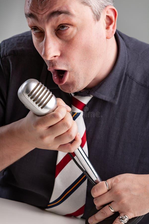 Hombre absorbido en su música que sostiene un micrófono fotografía de archivo libre de regalías