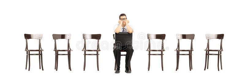 Hombre aburrido con la maleta que se sienta en un trabajo que espera de la silla para inter imagenes de archivo