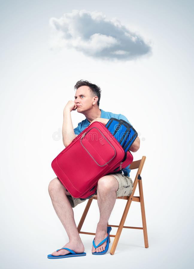Hombre aburrido en ropa del verano con una maleta roja que se sienta en esperar de la silla Sobre el jefe de una nube imagenes de archivo