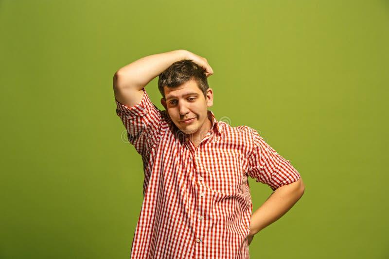 Hombre aburrido hermoso aislado en fondo verde fotografía de archivo