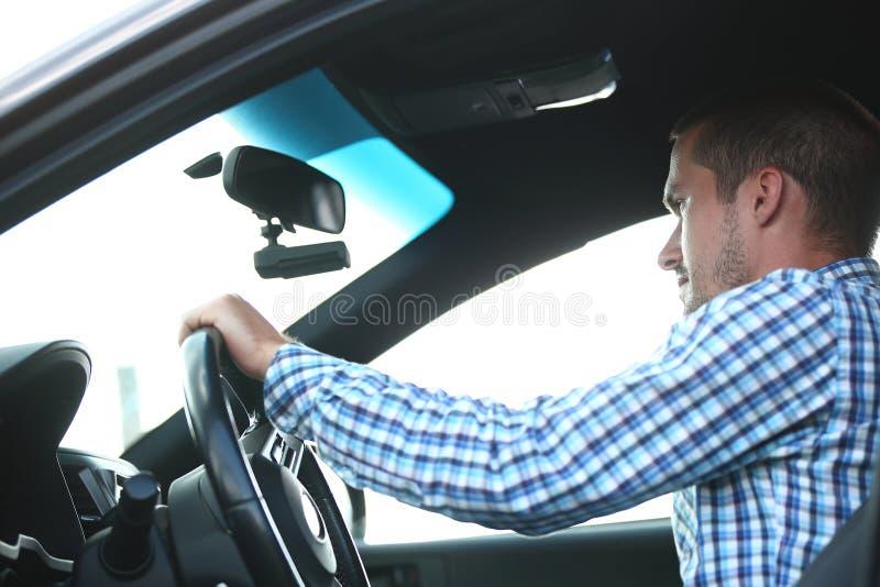 Hombre acertado joven que se sienta detrás de la rueda de un coche foto de archivo libre de regalías