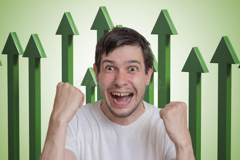 Hombre acertado y feliz joven y flechas verdes para arriba en fondo fotografía de archivo
