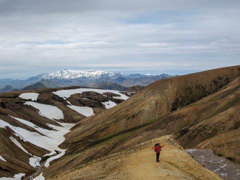 Hombre activo feliz que camina en montañas con la mochila pesada y los brazos abiertos de par en par Concepto de la aventura de l foto de archivo libre de regalías