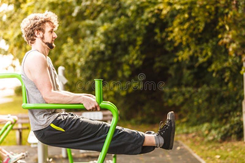 Hombre activo que ejercita en el aumento de la pierna al aire libre imágenes de archivo libres de regalías