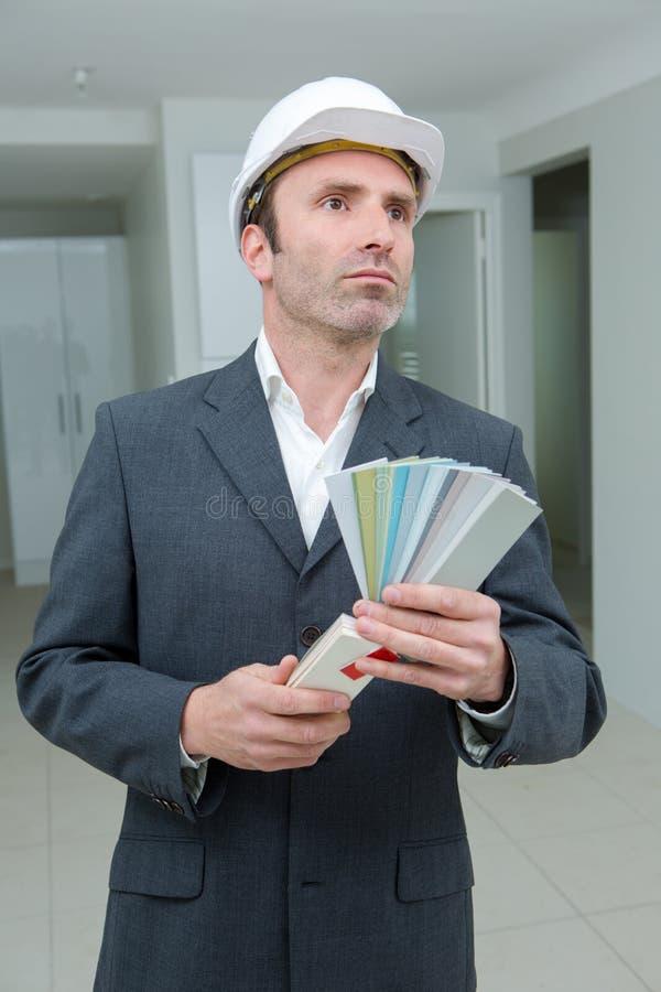 Hombre adecuado en el apartamento que sostiene muestras del color fotos de archivo