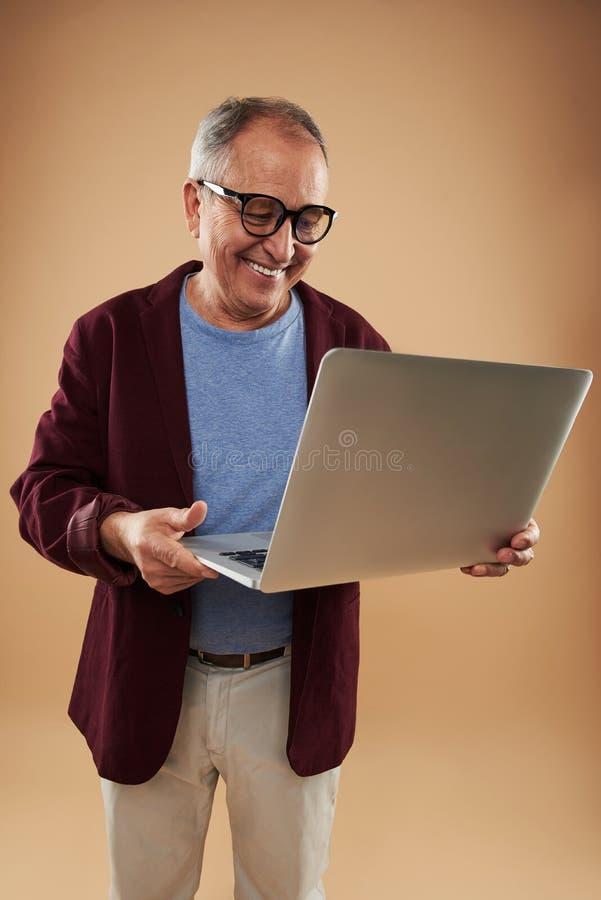 Hombre adulto alegre que celebra el ordenador portátil moderno y la sonrisa fotografía de archivo