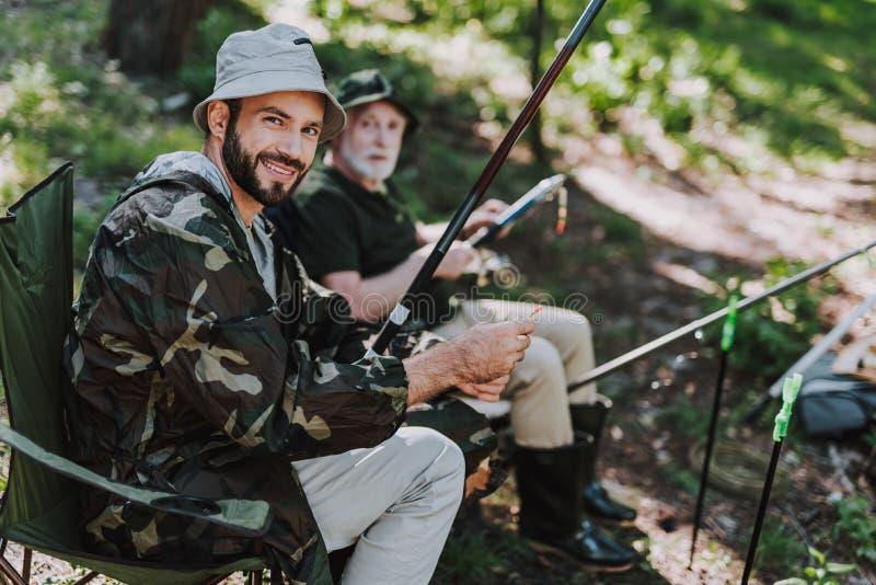 Hombre adulto alegre que pesca con su padre jubilado imagenes de archivo