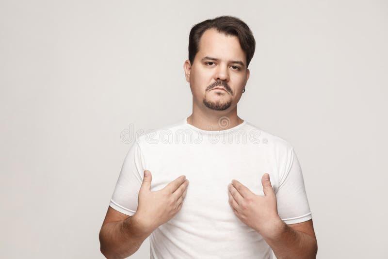 Hombre adulto arrogante y orgulloso que señala las manos mismas y mirada foto de archivo