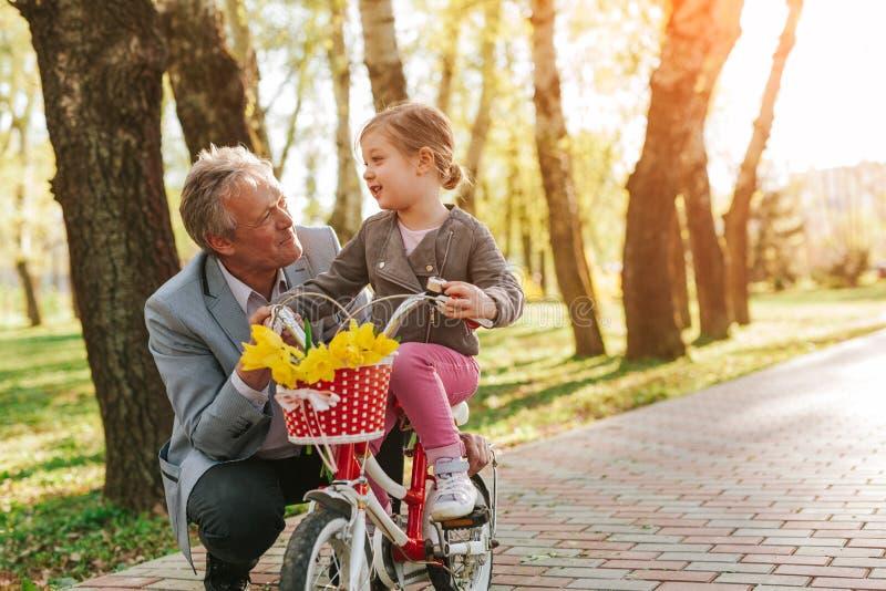 Hombre adulto con la nieta en la bici foto de archivo