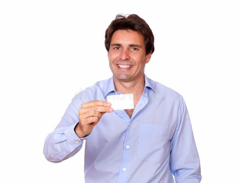 Hombre adulto elegante que sostiene una tarjeta de visita en blanco foto de archivo