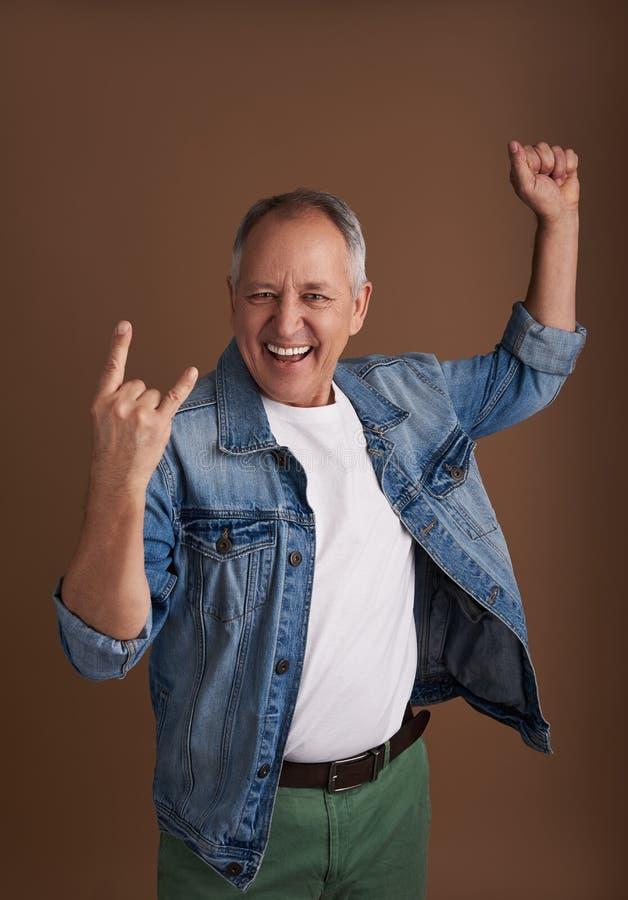 Hombre adulto emocionado que hace cuernos del diablo gesto y la sonrisa imagen de archivo libre de regalías