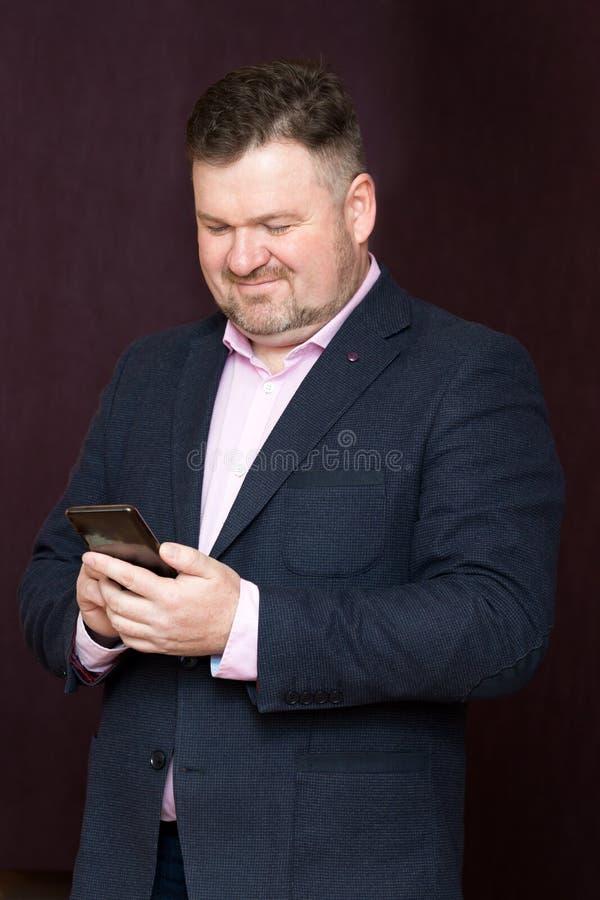 Hombre adulto en un traje con un teléfono fotos de archivo