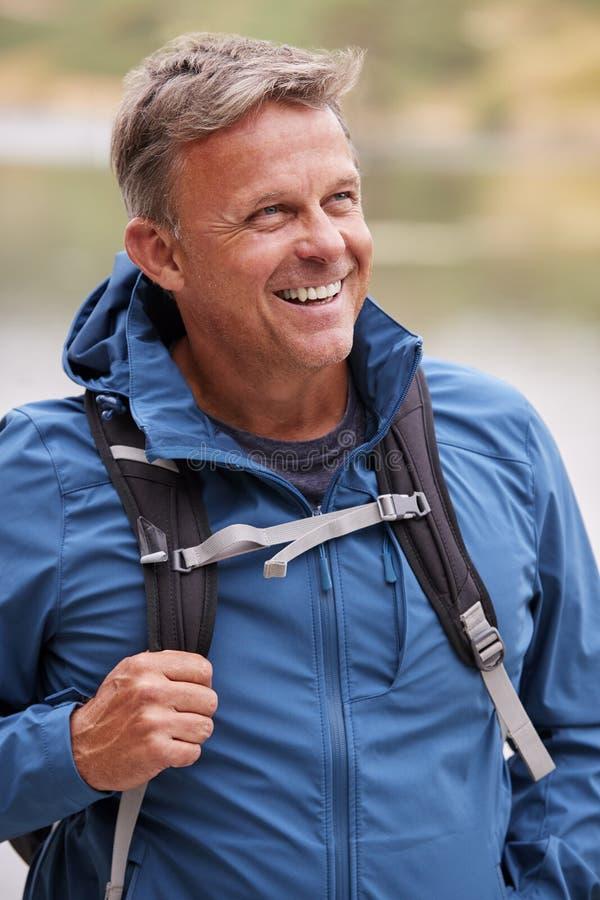 Hombre adulto en una acampada que mira lejos sonriendo, cerca para arriba, el distrito del lago, Reino Unido fotos de archivo libres de regalías