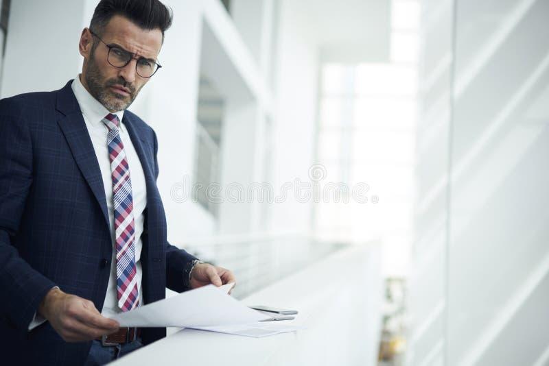 Hombre adulto en una chaqueta y los vidrios que crean procesos óptimos para mejorar renta del trabajo y del aumento imágenes de archivo libres de regalías