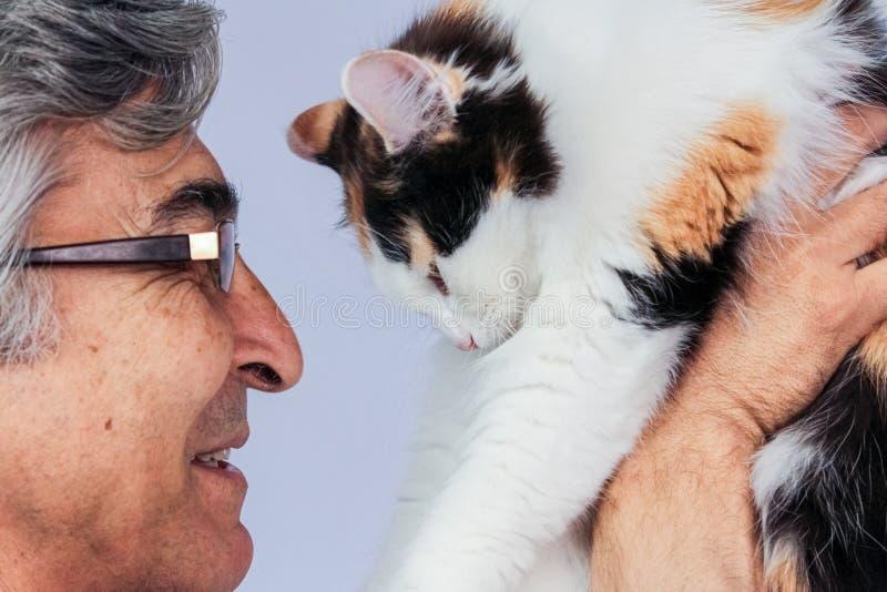 Hombre adulto feliz con las gafas que sostienen un gato tricolor cerca de su cara imagenes de archivo