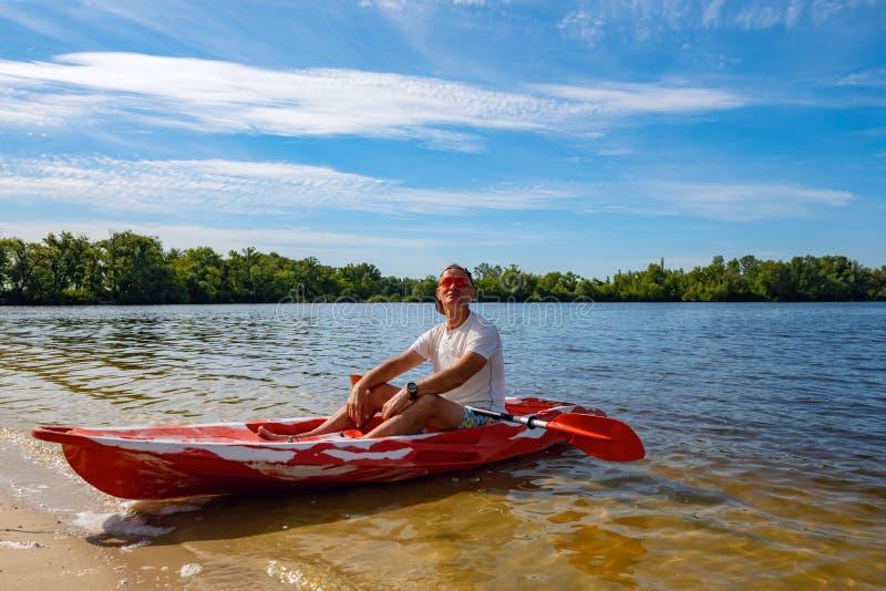 Hombre adulto feliz que se relaja en un kajak al lado de la playa imagen de archivo