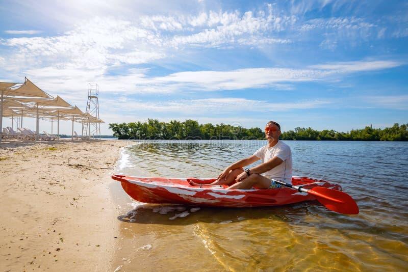 Hombre adulto feliz que se relaja en un kajak al lado de la playa fotos de archivo libres de regalías