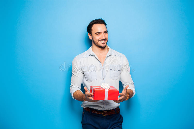 Hombre adulto hermoso en fondo azul con el regalo de la Navidad foto de archivo libre de regalías