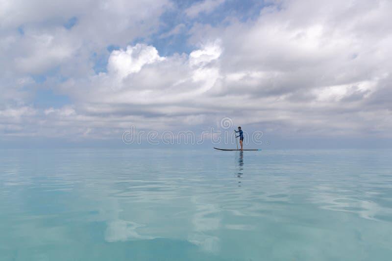Hombre adulto joven con del levantar la paleta en agua azul clara imagenes de archivo
