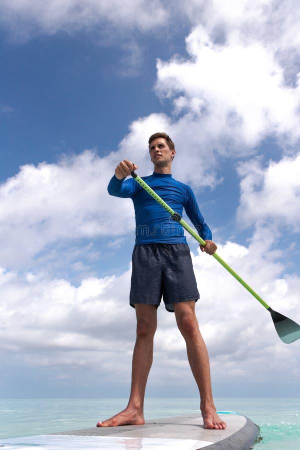 Hombre adulto joven con del levantar la paleta en agua azul clara imagen de archivo libre de regalías