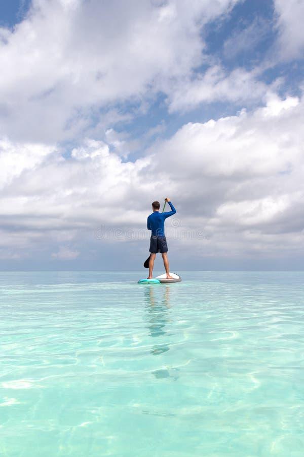 Hombre adulto joven con del levantar la paleta en agua azul clara fotos de archivo libres de regalías