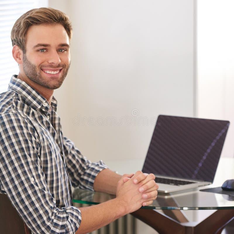 Hombre adulto joven hermoso que sonríe en la cámara sobre su hombro fotos de archivo libres de regalías