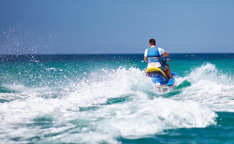 Hombre adulto joven que funciona con la onda en el esquí del jet durante vacaciones de verano imagenes de archivo