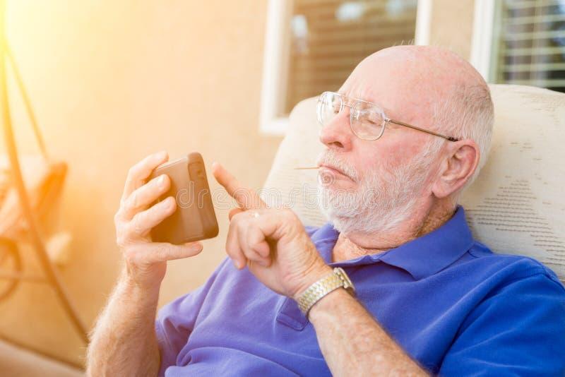Hombre adulto mayor que manda un SMS en el teléfono celular elegante imagen de archivo libre de regalías