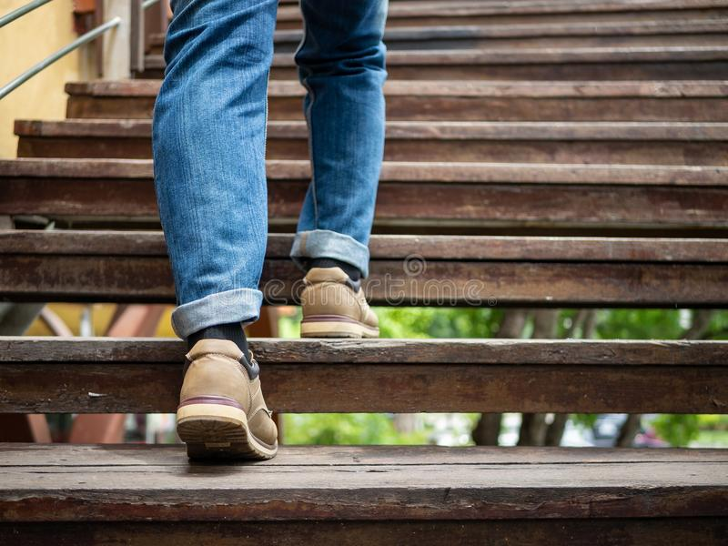 Hombre adulto que camina encima de las escaleras de madera Mudanza adelante de concepto fotos de archivo
