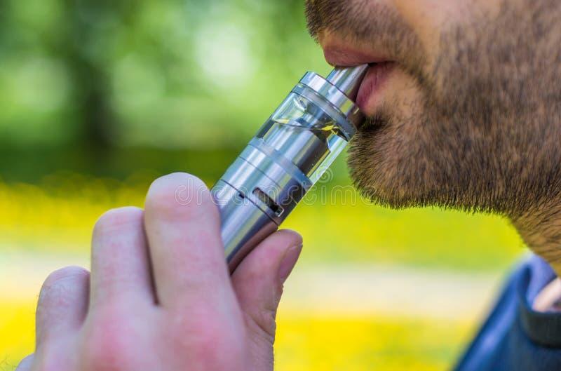 Hombre adulto que fuma un e-cigarrillo del vape en el parque imágenes de archivo libres de regalías