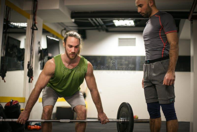 Hombre adulto que hace levantamiento de pesas en un gimnasio imagen de archivo libre de regalías