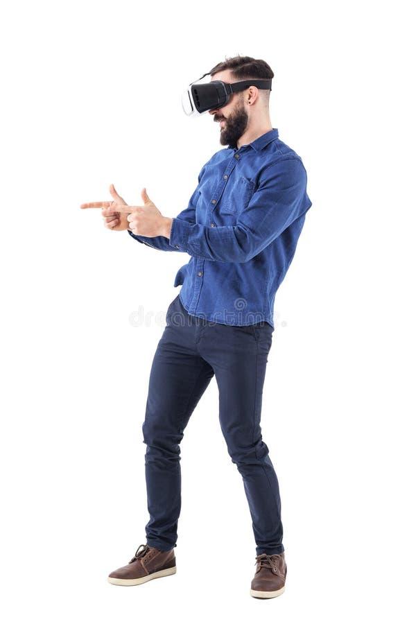 Hombre adulto que lleva los vidrios de la realidad virtual que juegan a los videojuegos que simulan la pistola con gesto del arma fotos de archivo libres de regalías