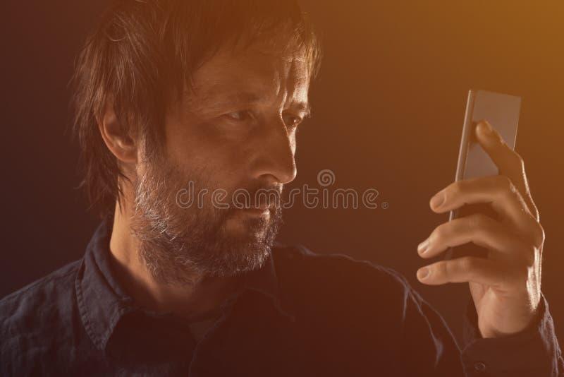 Hombre adulto que mira la pantalla del teléfono móvil fotografía de archivo libre de regalías