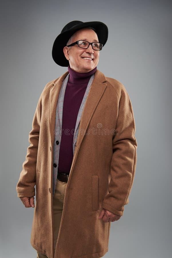 Hombre adulto que sonríe mientras que lleva la capa y el sombrero largos fotografía de archivo libre de regalías