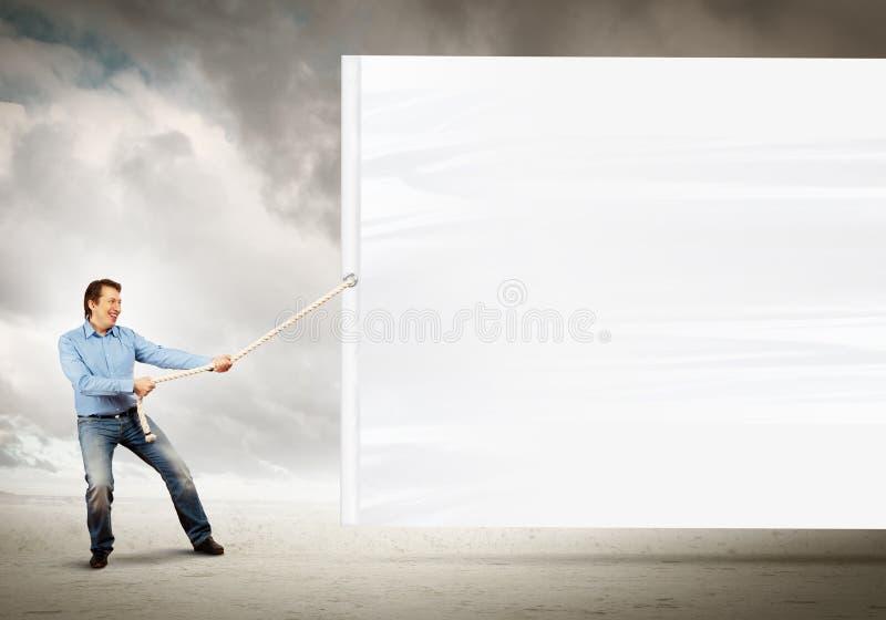 Hombre adulto que tira de la bandera en blanco fotos de archivo