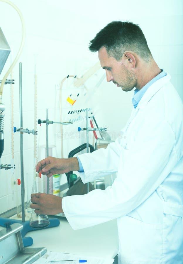 Hombre adulto que trabaja en la calidad de productos en laboratorio imagenes de archivo