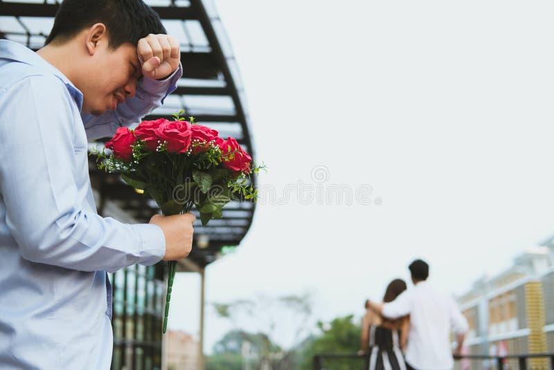 Hombre afligido que sostiene el ramo de rosas rojas que sienten tristes mientras que s fotografía de archivo libre de regalías